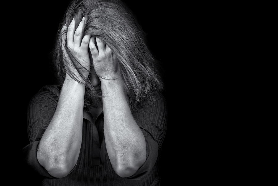 Black and white image of a young woman crying useful to illustra