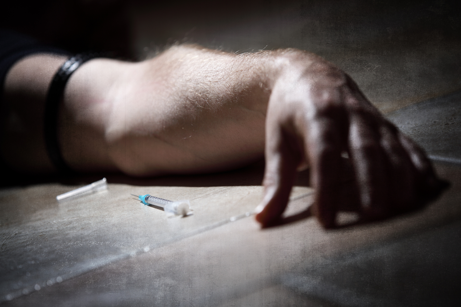 Drug addict with syringe lying down on the floor concept for sel