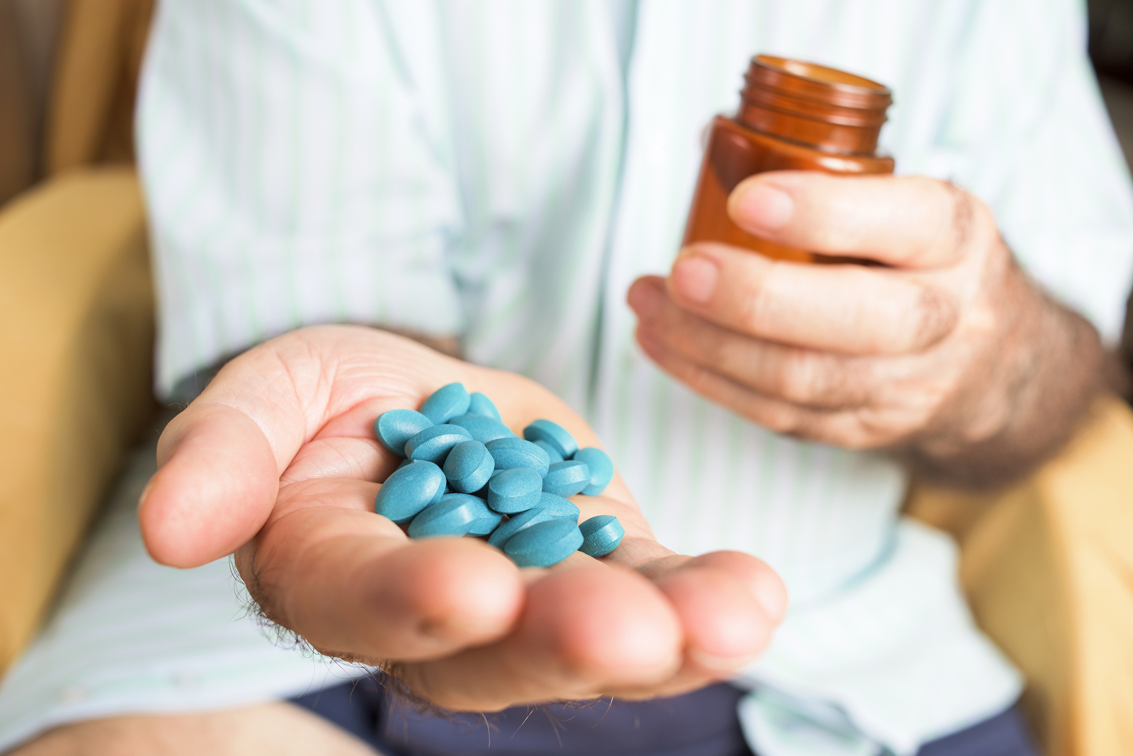 closeup of an old caucasian man with a pile of blue pills in his