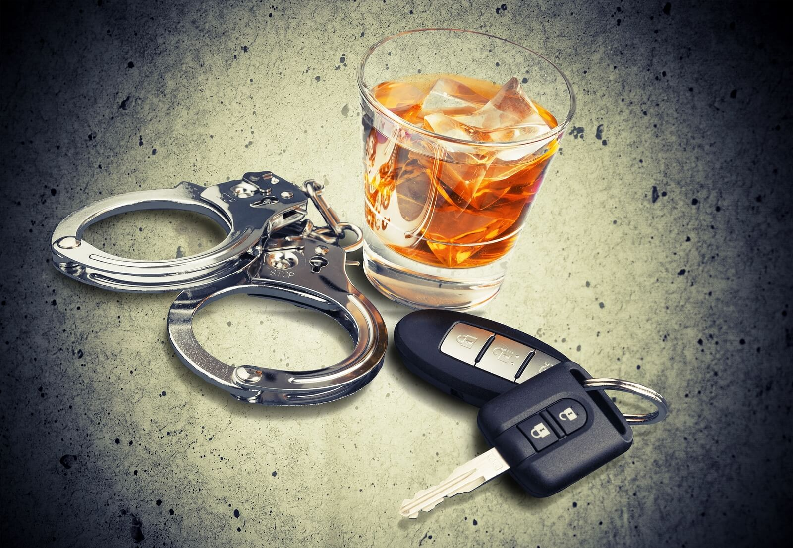 alcohol, keys, and handcuffs on table