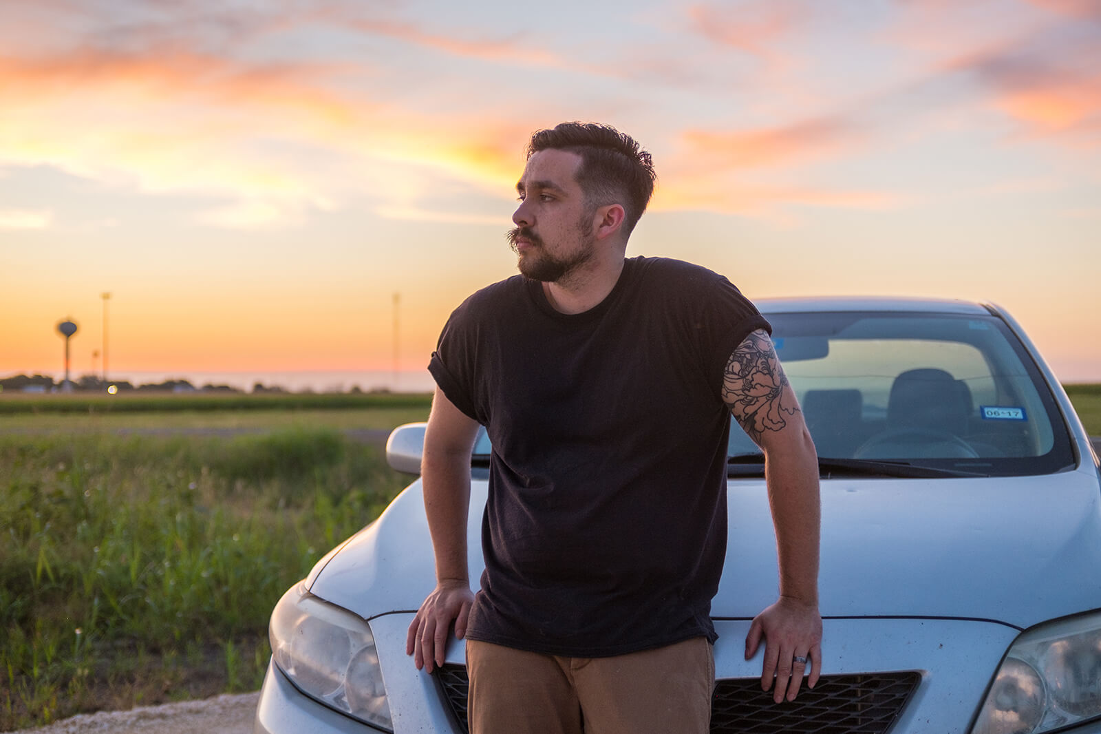 Man leaning on car with sunset in background