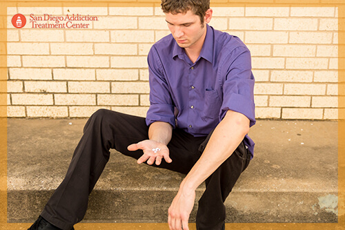 man sitting down staring at pills in hand