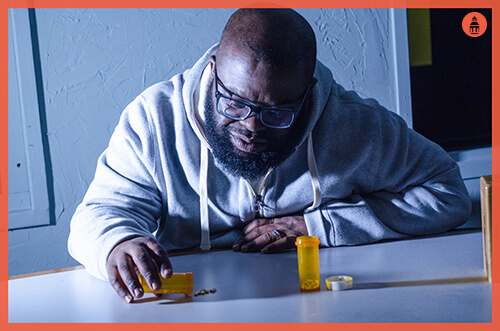 man with ambien addiction staring at pills on table